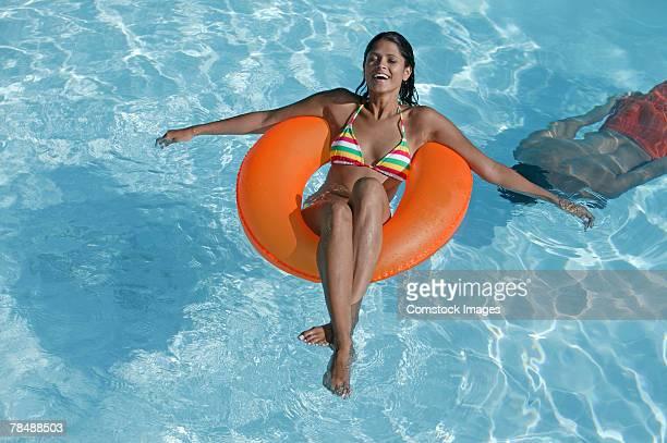 Woman floating on inner tube in swimming pool