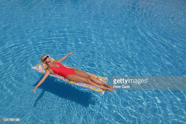 woman floating on lilo in pool