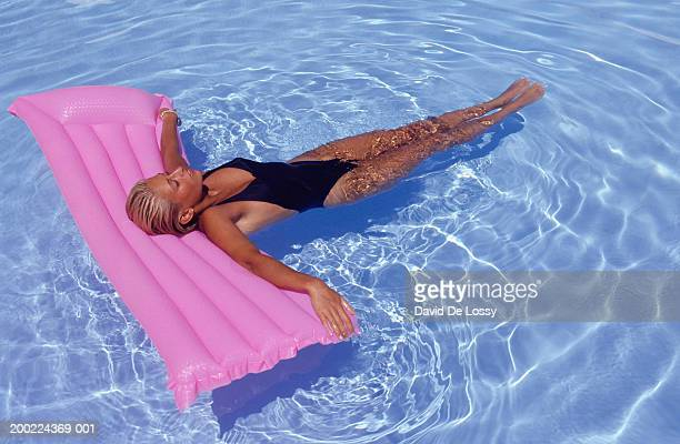Woman floating on raft in pool, elevated view