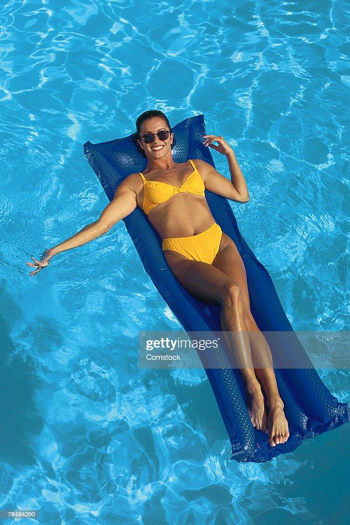 Woman floating on raft in swimming pool : Stockfoto