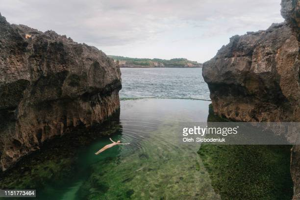woman floating on water in angel's billabong, nusa penida - billabong water stock photos and pictures