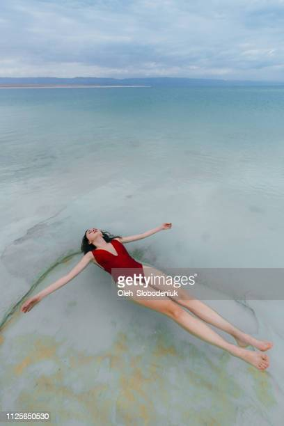 woman floating on water  in dead sea - dead sea stock pictures, royalty-free photos & images