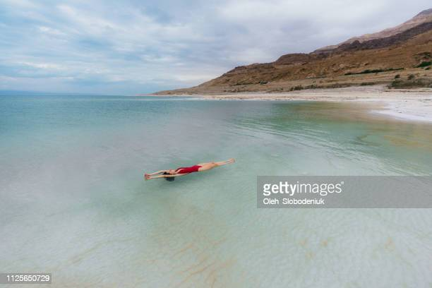 woman floating on water  in dead sea - jordan stock pictures, royalty-free photos & images