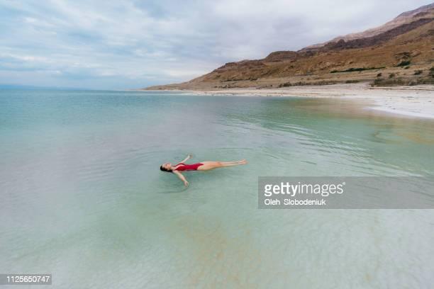 mujer flotando en el agua en el mar muerto - mar muerto fotografías e imágenes de stock