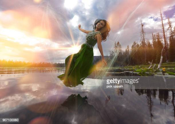 Woman floating over mountain lake