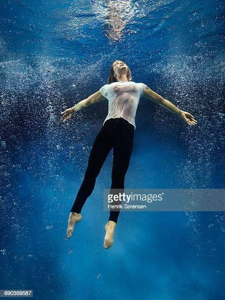 woman floating toward the surface - women in see through shirts stock photos and pictures