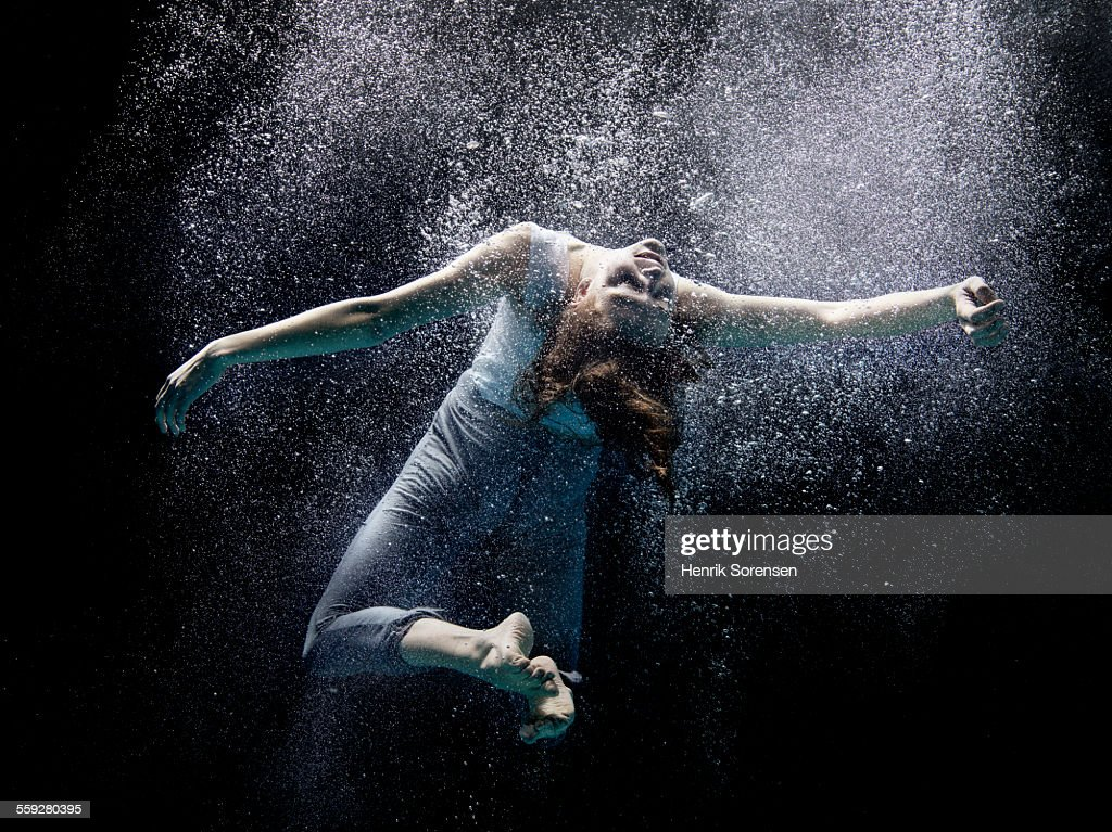 woman floating under water stock photo