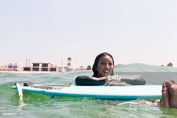 Woman floating with surfboard, Hermosa Beach, California, USA