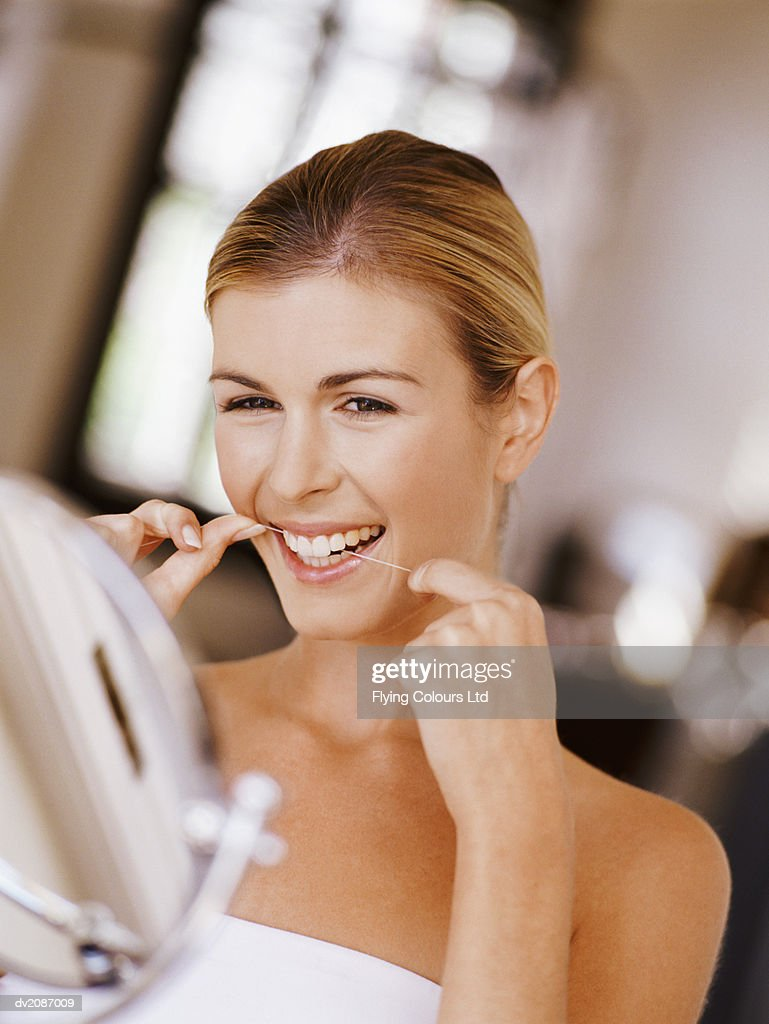 Woman Flossing Her Teeth : Stock Photo