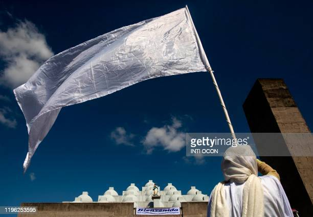 A woman flutters a white flag as the image of the Virgin of Fatima uarrives from Portugal to the Cathedral in Managua on January 25 2020