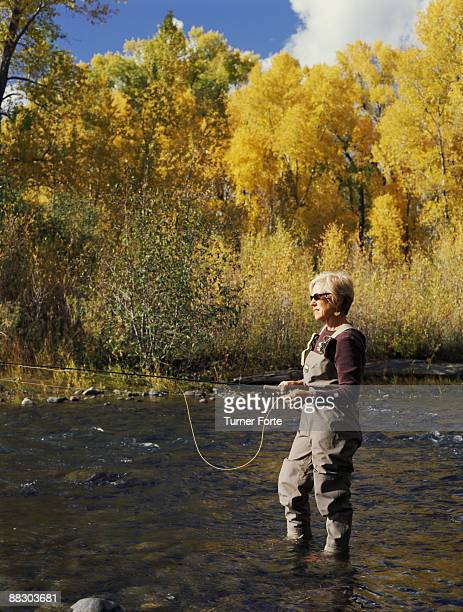 Woman fly fishing in stream , Rio Chama , New Mexico