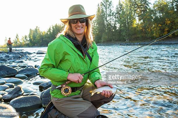 Woman fly fishing, rod & line caught trout, Canada