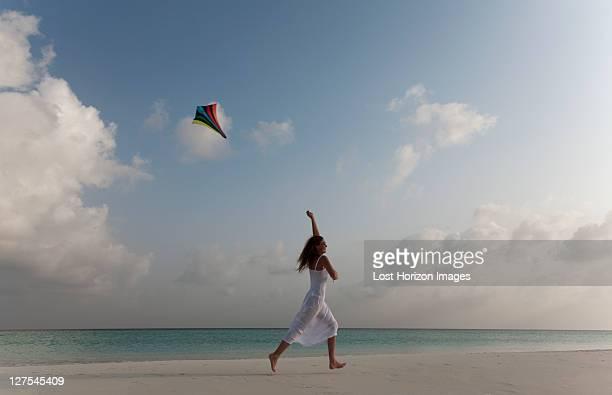 Woman flying a kite on tropical beach