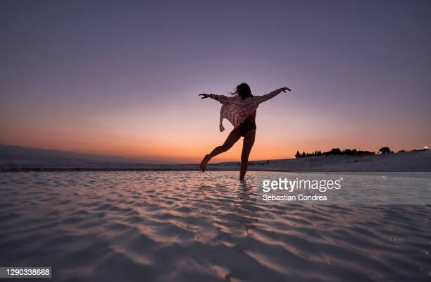 woman flying at travertine terraces in pamukkale at night, turkey. - royal tour stock pictures, royalty-free photos & images