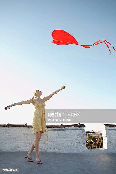 Woman flying heart-shaped red kite