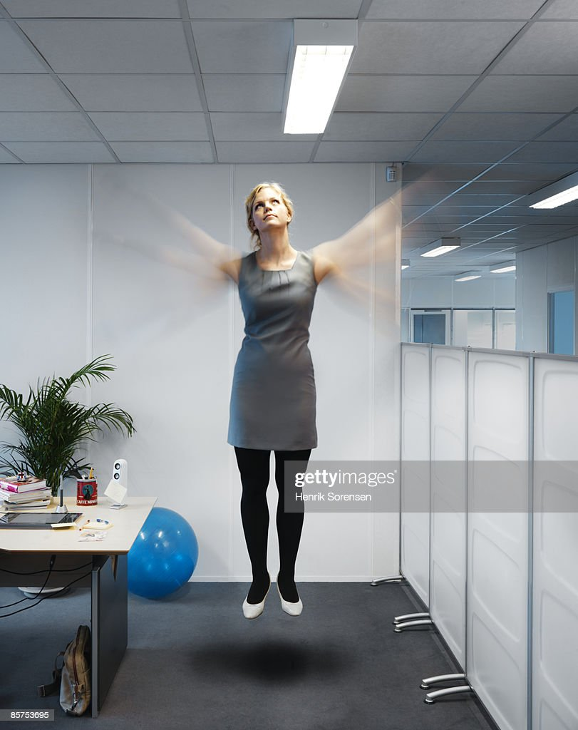 Woman flying in her office. : Stock Photo