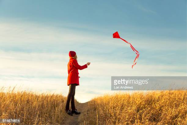Woman flying kite in prairies