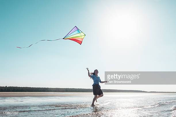 Woman flying kite on beach