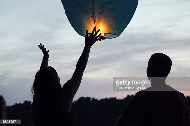 woman flying lit paper lantern during sunset - lantern stock photos and pictures