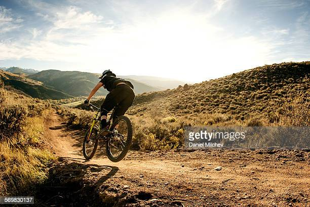 Woman flying on a downhill mountain bike.