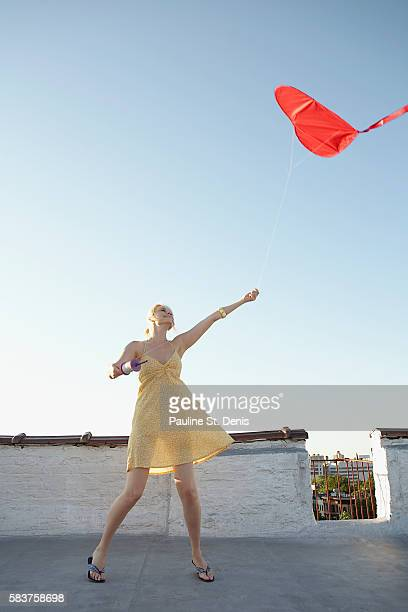 Woman flying red kite on rooftop