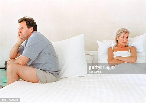 Woman folding arms, man sitting on side of bed