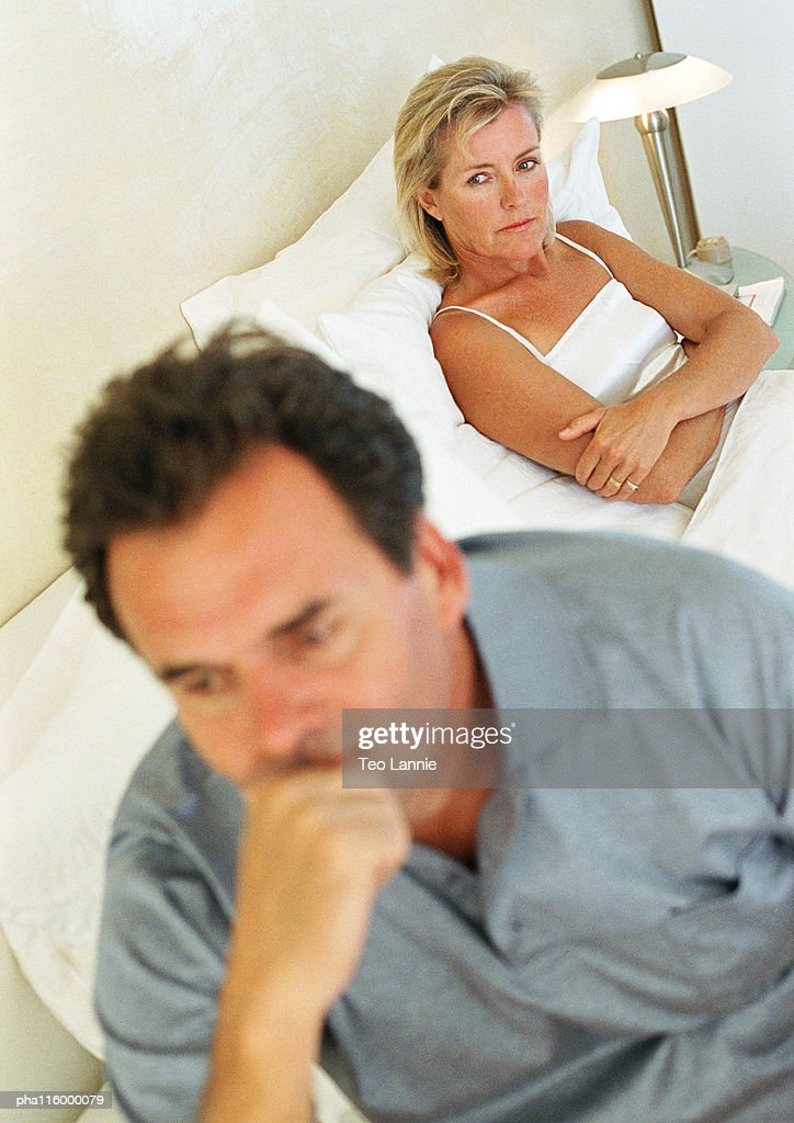 Woman folding arms, man sitting on side of bed : Stockfoto