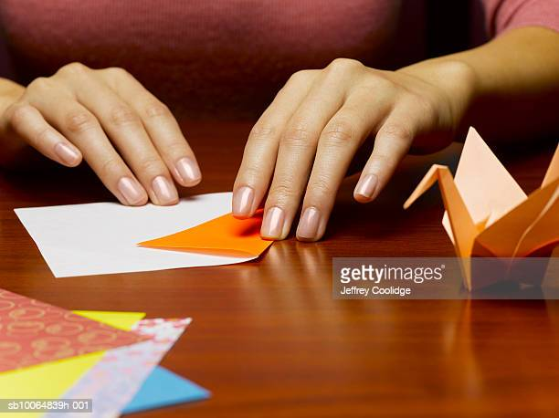Woman folding origami, mid section