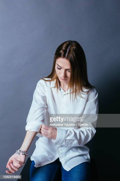 woman folding sleeve against gray background - vertikal stock-fotos und bilder
