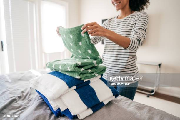 woman folding towels - mixing stock pictures, royalty-free photos & images