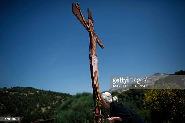 Woman follower of the Greek Orthodox Church kisses the feet of an image of Jesus crucified during the ceremony marking the Apokathelosis, the removal...