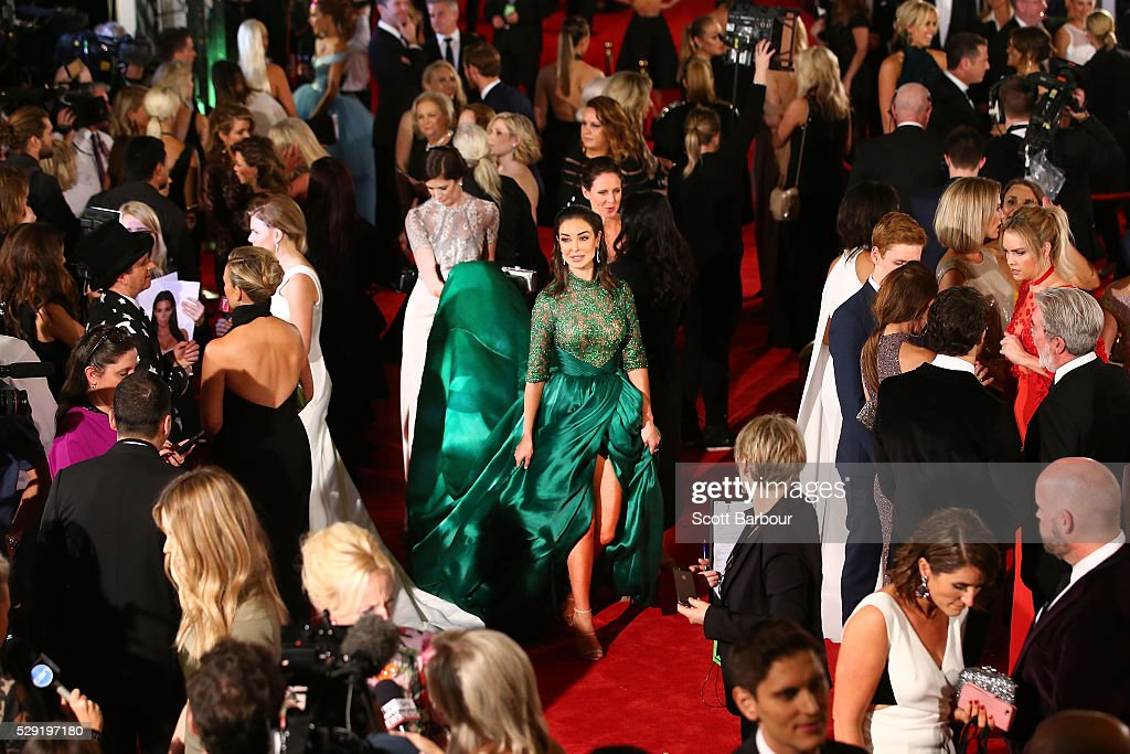 A woman follows Laurina Fleure carrying her long dress as she arrives at the 58th Annual Logie Awards at Crown Palladium on May 8, 2016 in Melbourne, Australia.