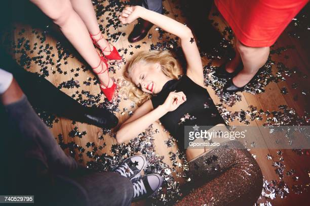 woman fooling around on floor at party, friends standing around her, glitter on floor, elevated view - drunk woman stock photos and pictures