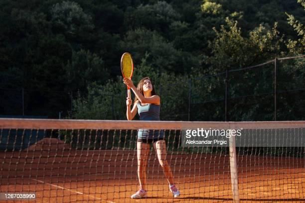 frau spielt kraftvoll tennis - einzelveranstaltung stock-fotos und bilder