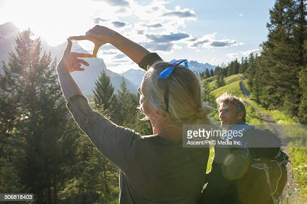 Woman frames mtns with hands as companion looks on