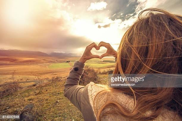woman frames nature into heart shape finger frame - dedos fazendo moldura - fotografias e filmes do acervo