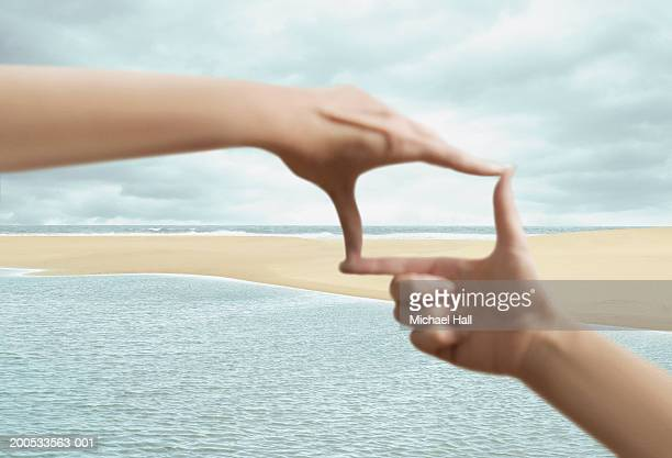 Woman framing beach with hands, close-up