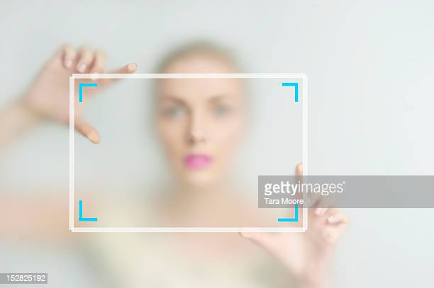 woman framing picture with hands