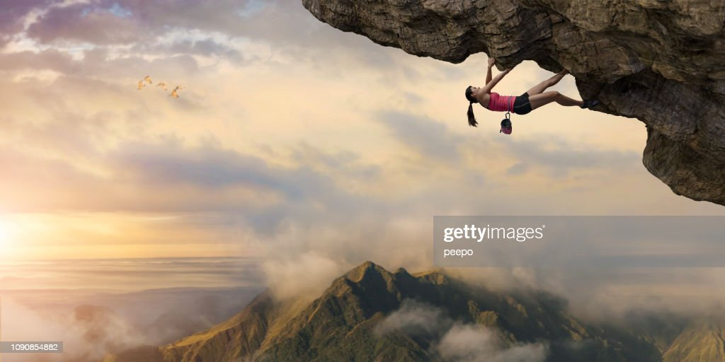 Woman Free Climber Climbs Overhang High Above Mountains at Dawn : Stock Photo