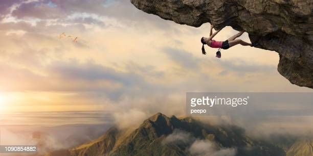 woman free climber climbs overhang high above mountains at dawn - adversidade imagens e fotografias de stock