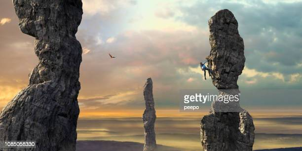 Woman Free Climber Scales High Column Of Rock At Dawn