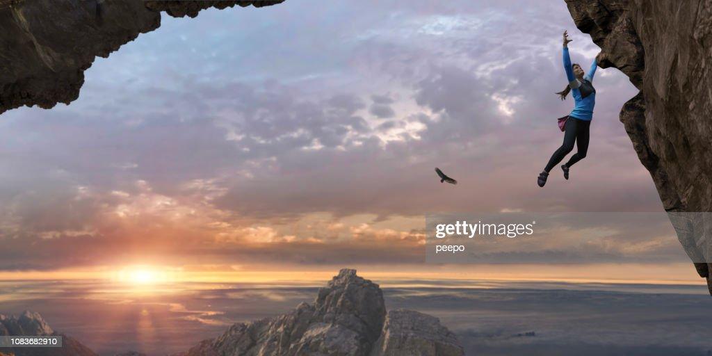 Woman Free Climbing Sheer Rock Face High Up At Sunrise : Stock Photo