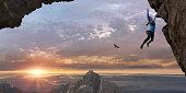 Woman Free Climbing Sheer Rock Face High Up At Sunrise