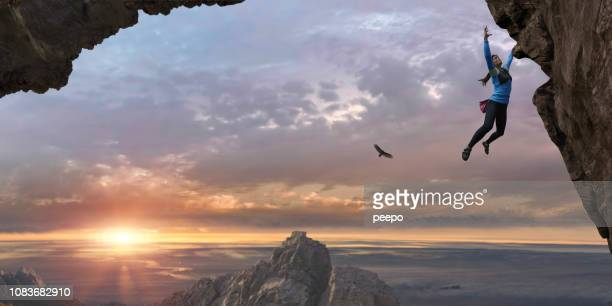woman free climbing sheer rock face high up at sunrise - coraggio foto e immagini stock
