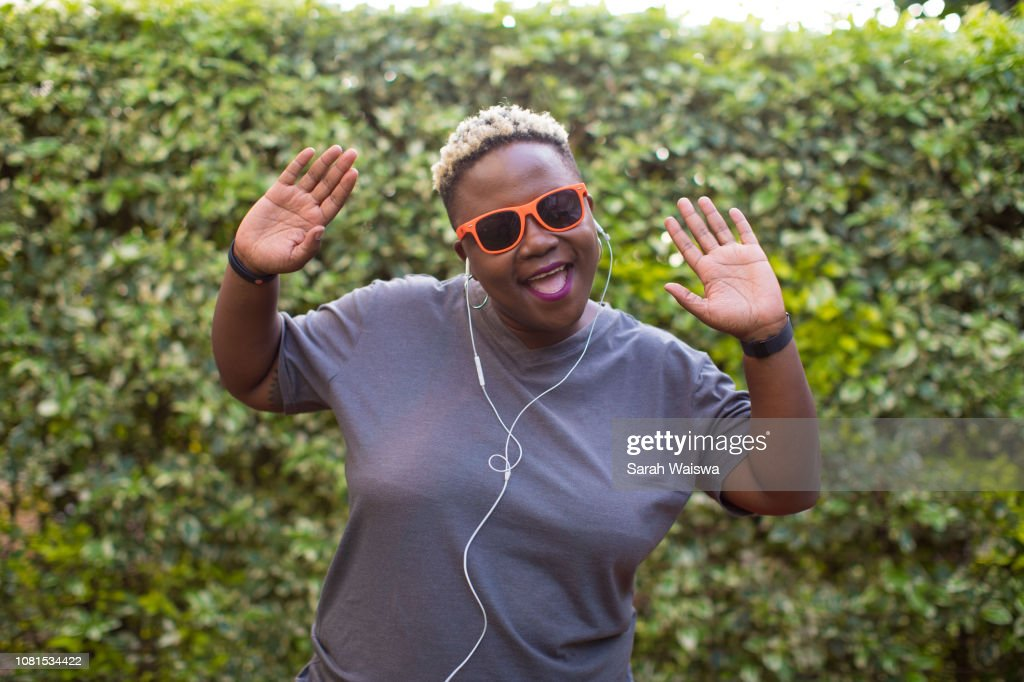 Portrait of a black woman listening to music outside with hands in the air : Stock Photo