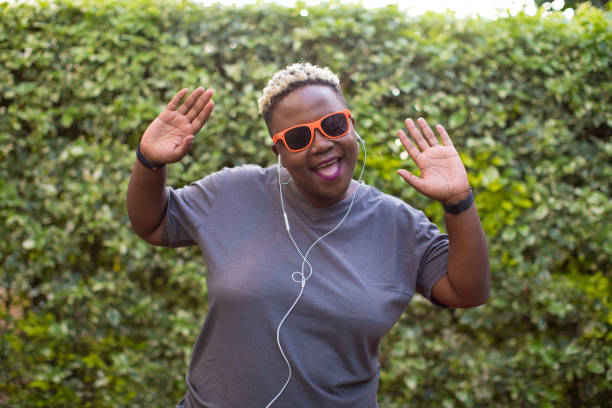 Portrait of a black woman listening to music outside with hands in the air