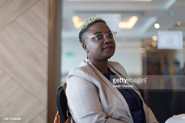 portrait of black business woman listening at a conference - nairobi stock pictures, royalty-free photos & images