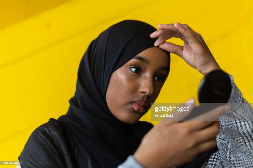 Black woman in hijab in front of yellow wall : Stock-Foto