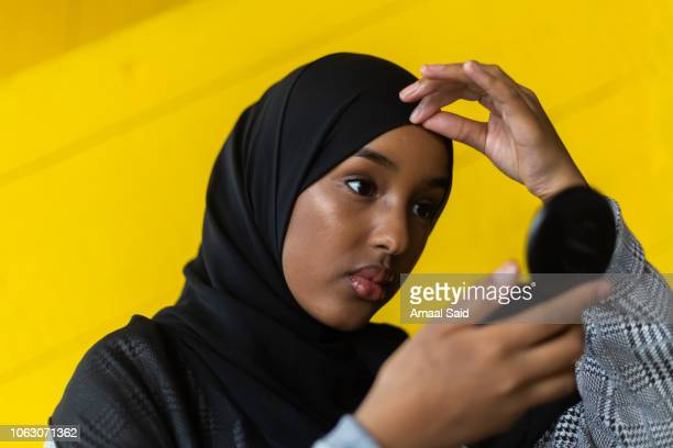 Black woman in hijab in front of yellow wall
