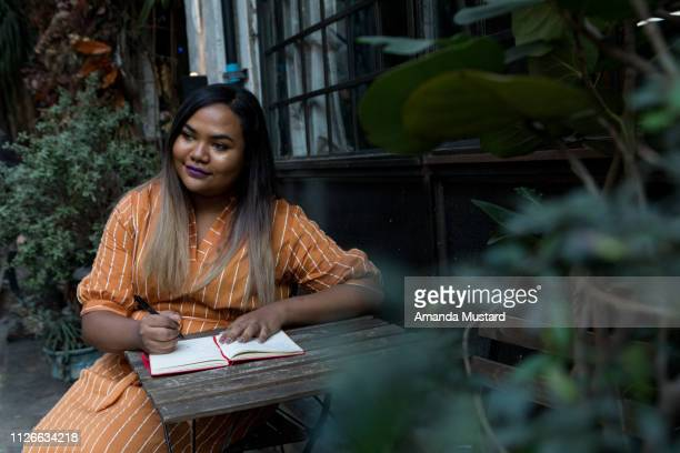 young mixed race woman writing in journal - curvy asian woman stock pictures, royalty-free photos & images